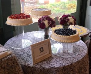 dessert table with three cakes on tall stands and flowers