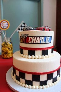 racing themed birthday cake with two cars on top