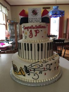 tall music theme cake with congratulations written on it