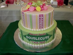 Two tier round cake with each tier having different design for twins