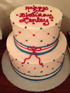 two tier birthday cake with pink and blue dots