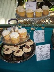 table with two platters of vanilla and chocolate cupcakes