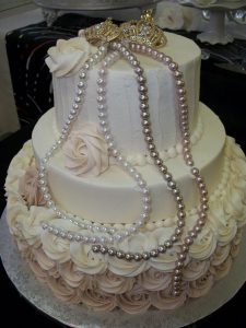 powder pink and white cake with pearls and two small crowns on top