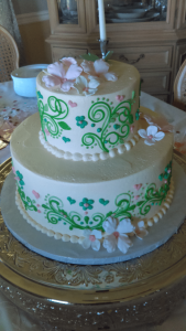 white cake with pale pink flowers and bright green design