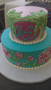 Pink and teal cake with initials and palm trees