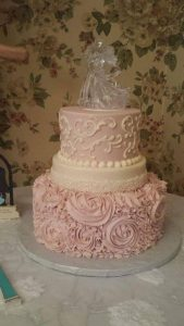 delicate pink and white two tier cake with glass topper