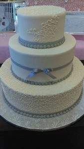 all white wedding cake with small silver bow tie