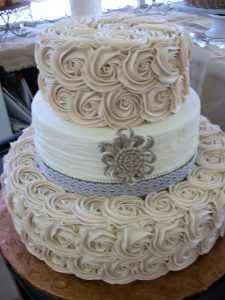 ivory wedding cake with white tier in between two ivory creme roses tiers