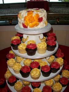 red and yellow wedding cupcake tower with pop of orange on the top