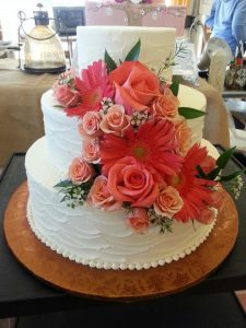 plain white wedding cake with coral flowers