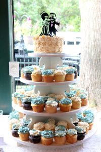 cup cake stand with wedding cake on top layer