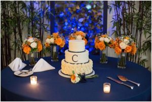 white three tier wedding cake with orange and white flowers on the background