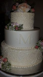 Layered wedding cake with monogram and live flowers