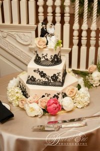 square asymmetrical three tier wedding cake with lattice and flower decor