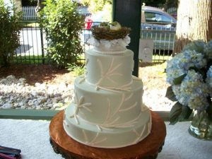 delicate four tier wedding cake with the bird nest topper