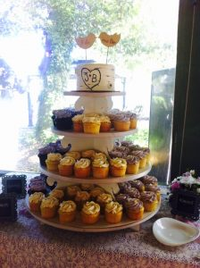 wedding cupcake tower with two lovebirds as a topper