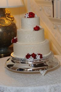 white shiny wedding cake with red roses