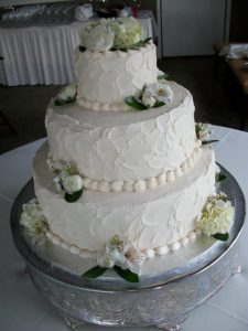 white three tier wedding cake with live flowers