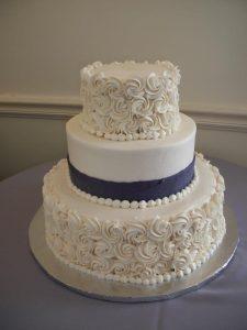 White wedding cake with creme roses