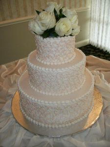 three tier wedding cake with roses on top