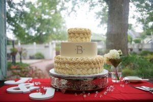 Ivory monogram wedding cake with creme roses